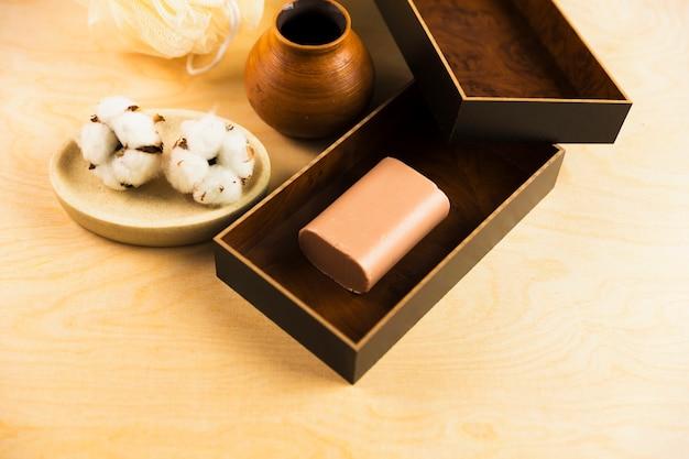 Boule de coton brut et barre de savon à base de plantes sur la table en bois