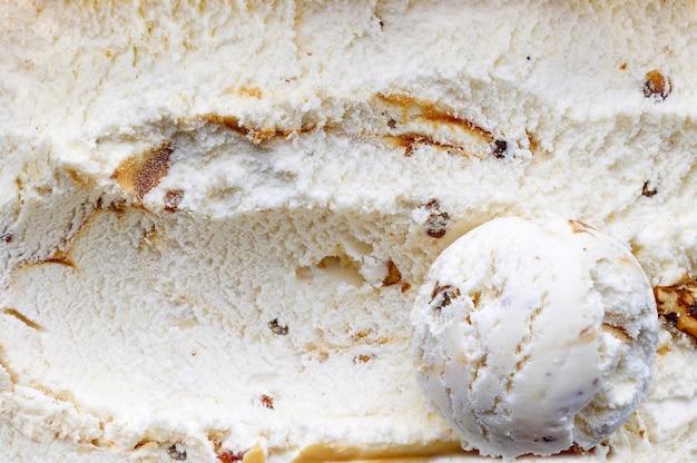 Boule de crème glacée sur fond de crème glacée aux noix caramélisées et au sirop d'érable, vue de dessus