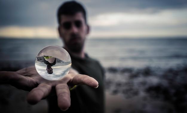 Boule de cristal sur la main sur la plage