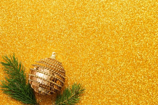 Boule décorative avec des branches d'arbres de noël sur fond de paillettes dorées