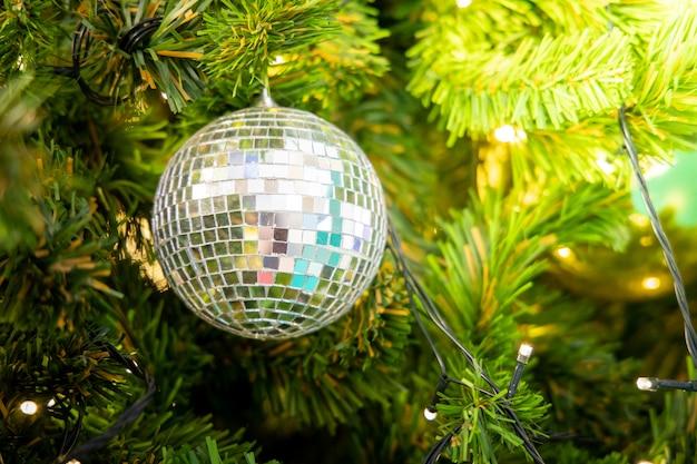 Boule disco accroché sur l'arbre de noël décoré