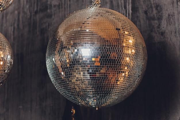 Boule disco scintillante suspendue dans une pièce crasseuse vide.