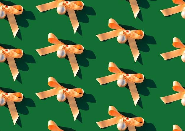 Boule dorée brillante de décoration de noël avec le ruban orange sur le fond vert
