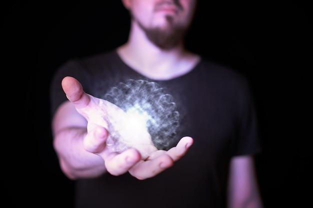 Boule d'énergie dans la main de l'assistant. homme barbu jetant un sort de boule magique lumineuse. fond noir