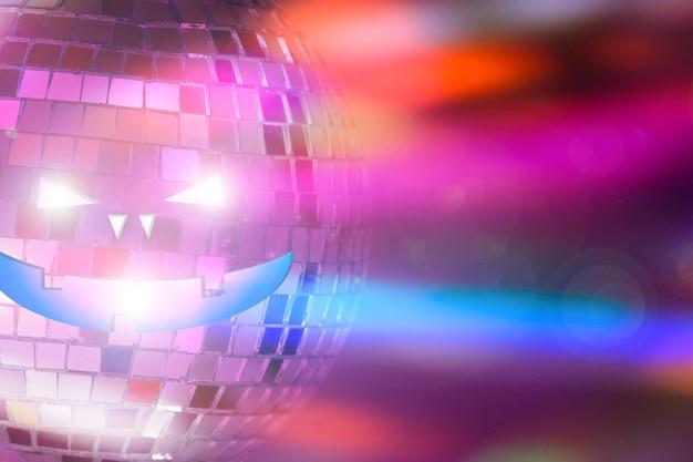 Boule à facettes avec visage halluin sur fond coloré avec reflets. photo de haute qualité