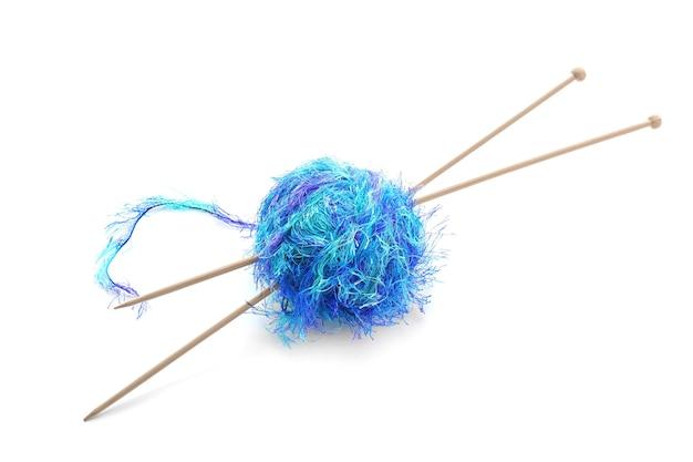 Boule de fil avec des aiguilles à tricoter sur blanc