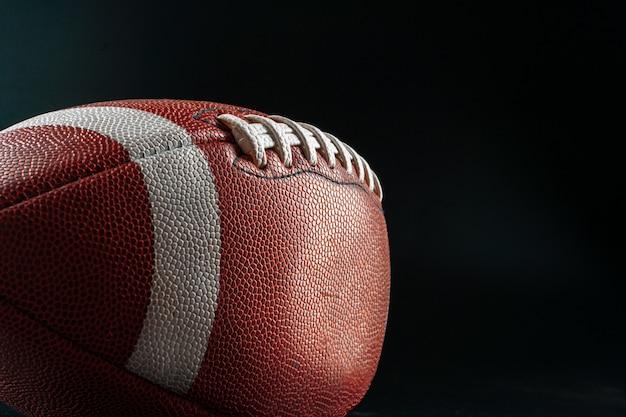 Boule de football américain sur fond sombre se bouchent. concept de football américain