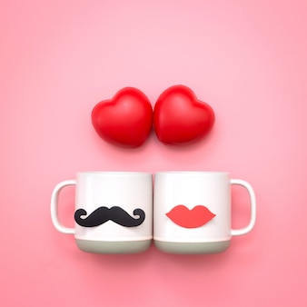 Boule en forme de coeur et papier faux décor de lèvres et moustaches sur une tasse rose sur fond rose.