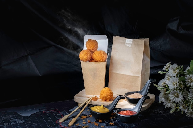 Boule de fromage dans un récipient en papier, fond chaud, fumé, noir