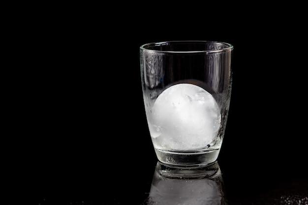 Boule de glace à l'intérieur du verre à cocktail sur une table noire réfléchissante.