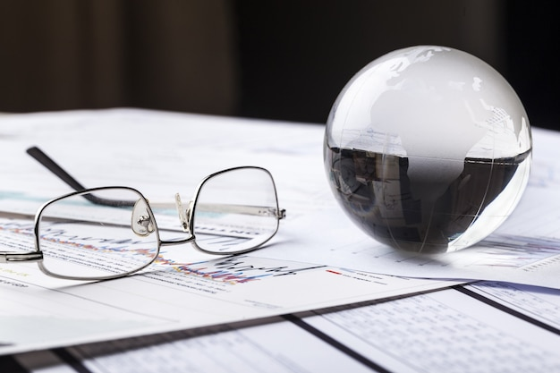 Boule de globe en verre avec des lunettes sur le fond des diagrammes d'affaires