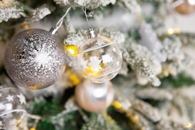Boule de jouet de noël accrochée à une branche d'épinette avec guirlande