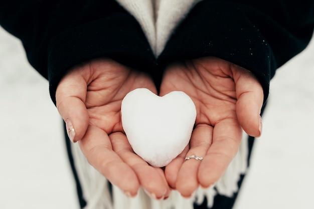 Boule de neige coeur neige dans les mains gantées de fille. arrière-plan flou. photo de haute qualité