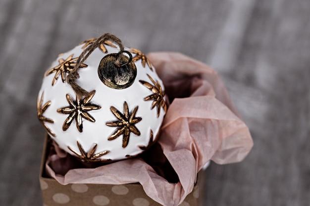 Boule de noël blanche ancienne, assise dans la boîte à cadeaux