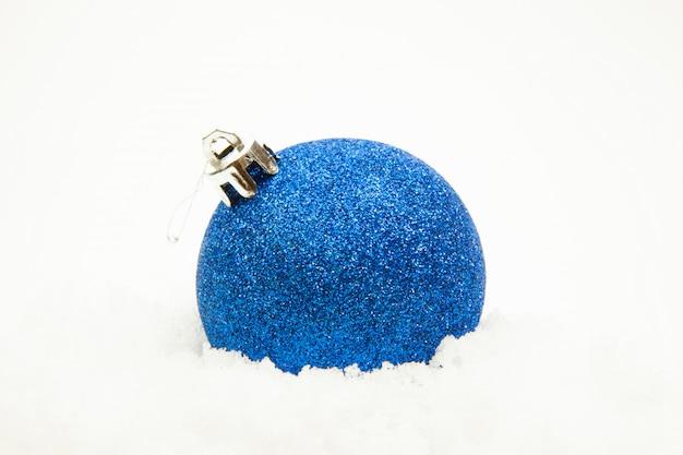 Boule de noël bleue sur la neige blanche, gros plan