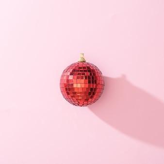 Boule de noël boule disco rouge sur fond rose. concept de fête de nouvel an minimal. mise à plat.