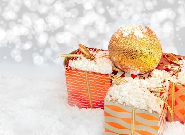 Boule de noël sur les cadeaux avec la neige