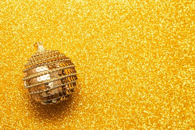 Boule de noël décorative sur fond de paillettes dorées