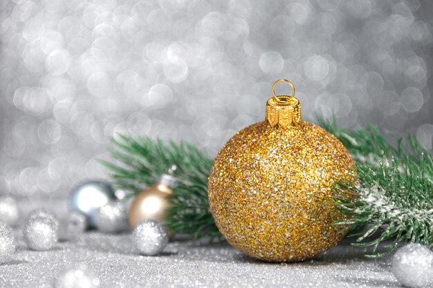 Boule de noël dorée sur fond de paillettes