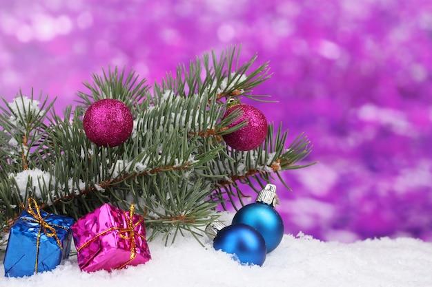 Boule de noël et jouet avec arbre vert dans la neige sur violet