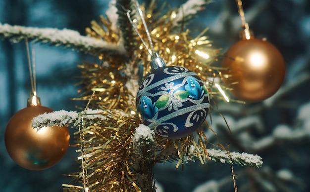 Boule de noël lumineuse d'une branche d'arbre de noël couverte de neige dans la forêt d'épinettes, espace de copie