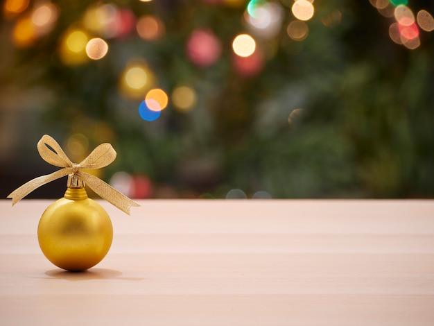 Boule de noël noeud de ruban d'or avec arbre de noël décoré flou et lumières bokeh en arrière-plan. espace pour le texte