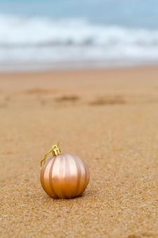 Boule de noël sur une plage de sable au bord de l'océan