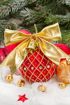 Boule de noël rouge et or avec noeud dans la neige