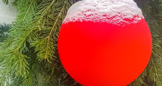 Une boule de noël rouge, recouverte de neige, sur fond de branche de sapin, décorations de noël à l'air libre, bannière.