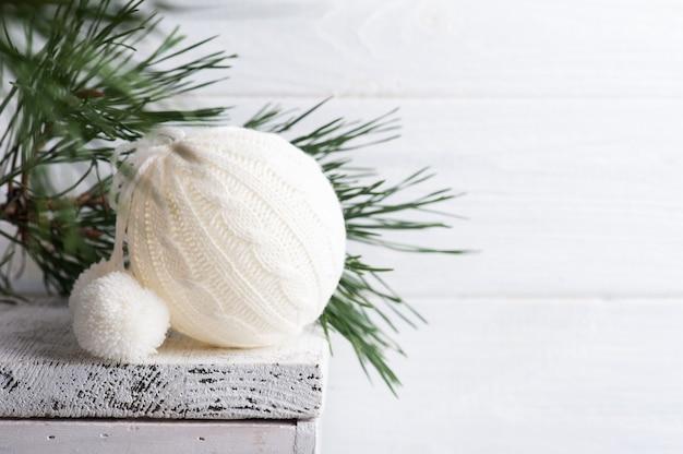 Boule de noël en tricot blanc et pin dans un intérieur scandinave blanc.