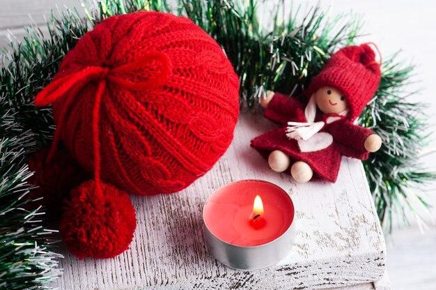 Boule de noël en tricot rouge et décoration avec bougie allumée dans un intérieur scandinave blanc. copier l'espace pour greting