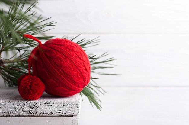 Boule de noël en tricot rouge et pin dans un intérieur scandinave blanc.