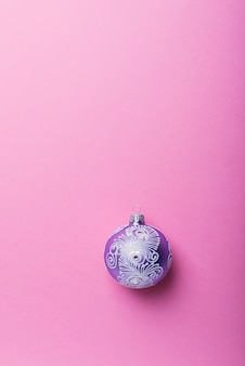 Boule de noël violet sur fond rose, concept de noël. vue de haut en bas avec espace de copie pour le texte
