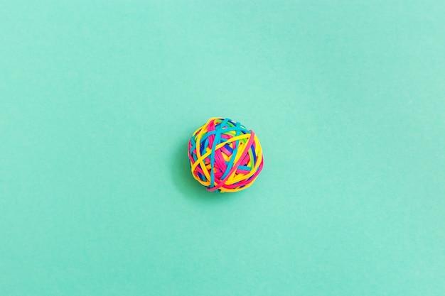 Boule ou nœud de minces caoutchoucs élastiques multicolores sur fond uni. enchevêtrement de pensées.