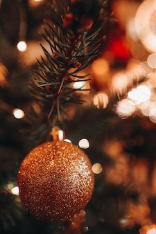 Boule d'or de jouet de noël accrochée à l'arbre de noël avec des lumières brillantes de bokeh sur l'arrière-plan