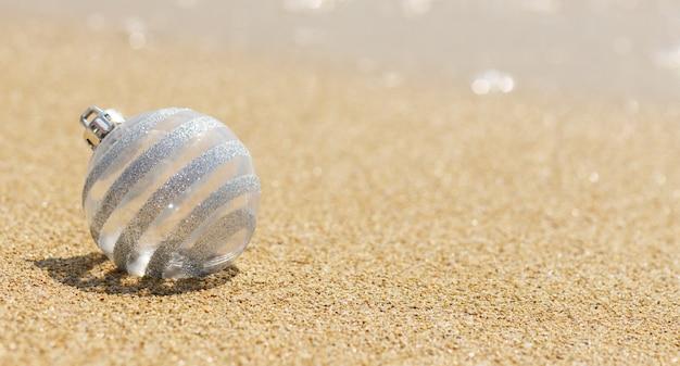 Boule de paillettes blanches de noël sur la plage tropicale près de l'océan, joyeux noël et bonne année