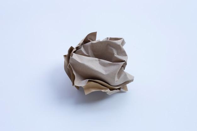 Boule de papier blanc froissé sur un mur sombre. copier l'espace