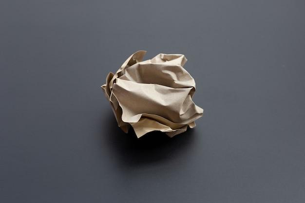 Boule de papier brun froissé sur une surface sombre. copier l'espace