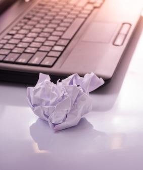 Boule de papier froissé avec fond d'ordinateur portable