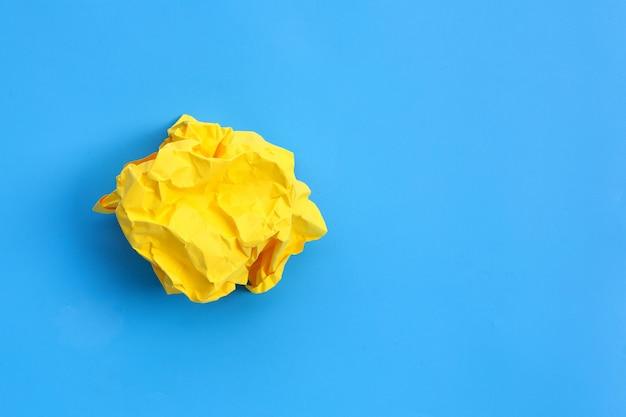 Boule de papier jaune froissé sur une surface bleue. vue de dessus