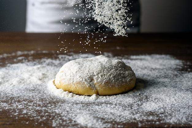Boule de pâte crue saupoudrée de farine blanche sur une table en bois. farine congelée dynamiquement en vol