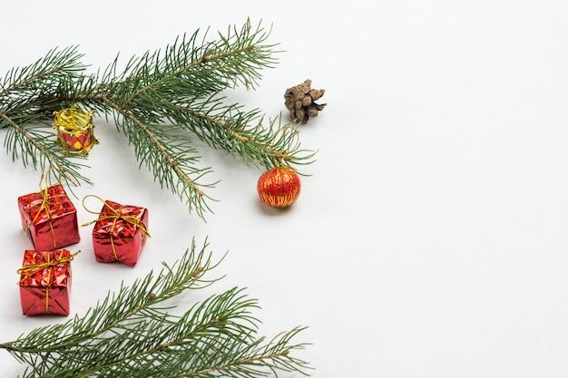 Boule rouge sur une branche de sapin. jouets de noël et branches de sapin sur fond blanc. copiez l'espace. mise à plat
