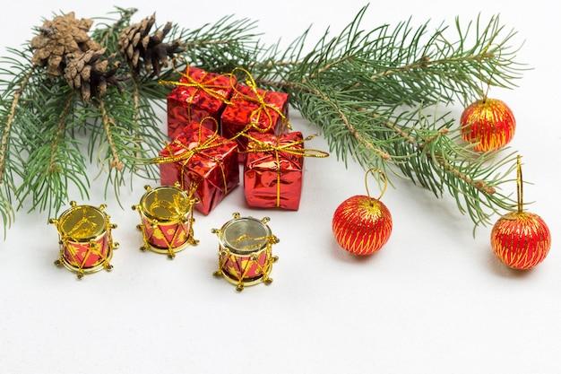 Boule rouge sur une branche de sapin. jouets de noël et branches de sapin sur une surface blanche. copiez l'espace. mise à plat