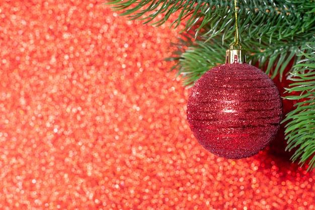 Boule rouge brillante sur une branche d'un arbre de noël sur un arrière-plan flou rouge.