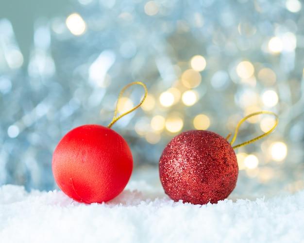 Boule rouge dans la neige sur fond de bokeh blanc,