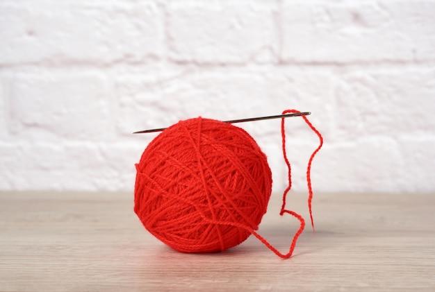 Boule rouge avec fil de laine et grande aiguille sur mur de briques blanches, gros plan