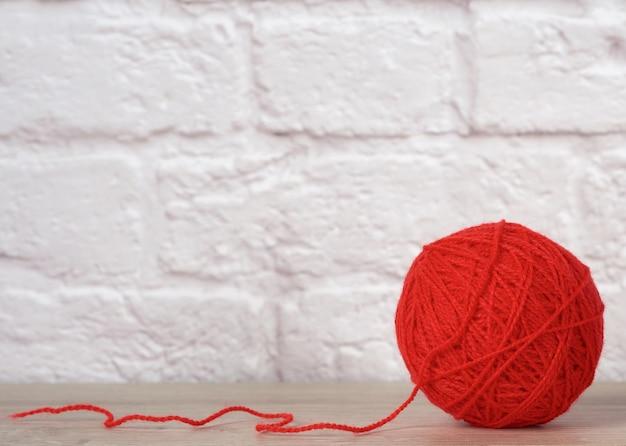 Boule rouge avec fil de laine sur mur de briques blanches, gros plan