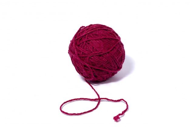 Boule rouge foncé de fil de laine, mur blanc isolé.