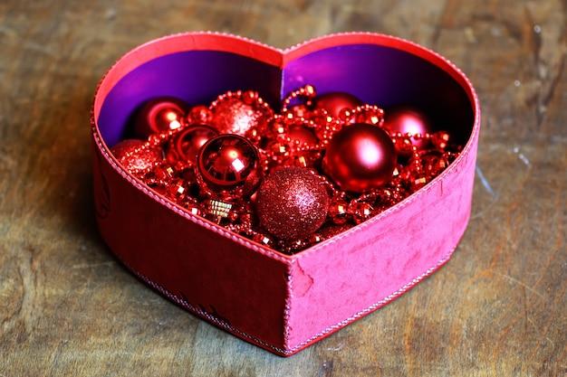 Boule rouge de noël dans un coeur de forme de boîte