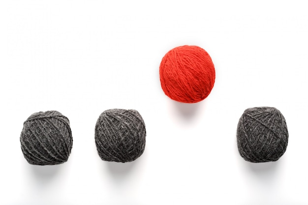 Une boule rouge unique saute d'une rangée de boules de laine identiques